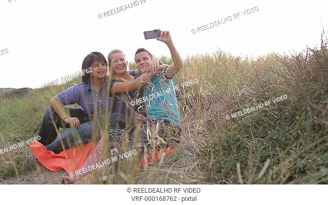 Group of teenagers picnic in sand dune and taking picture