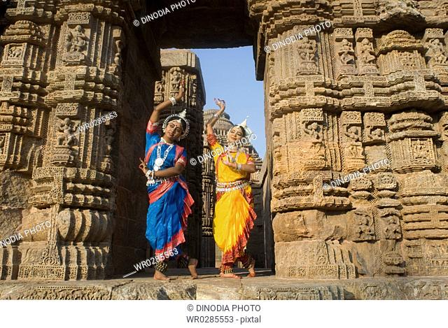 Odissi dancers strike pose re-enacts Indian myths such as Ramayana in front of world heritage Sun temple complex in Konarak , Orissa , India MR400