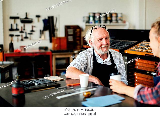 Senior craftsman sitting at table with young craftswoman and smiling in book arts workshop