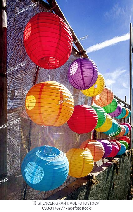 Afternoon sun shines through a colorful display of Chinese paper lanterns at an Asian American cultural festival in Costa Mesa, CA