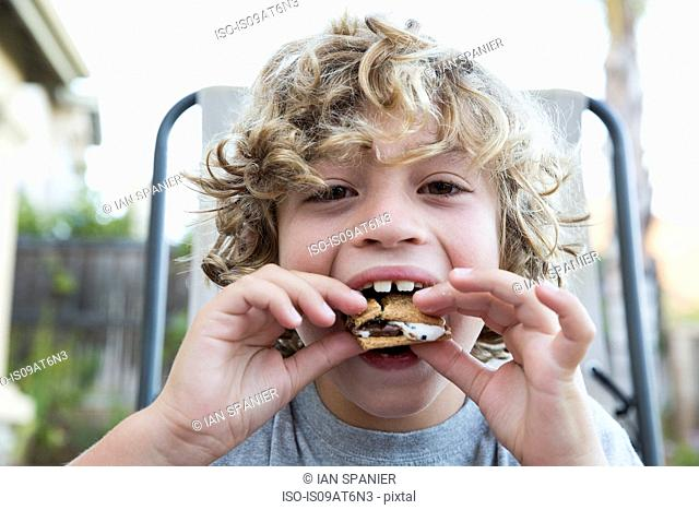 Close up portrait of boy eating a snack