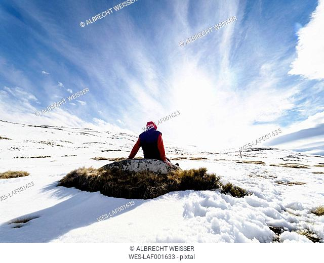 Spain, Sierra de Gredos, hiker sitting on rock in snow