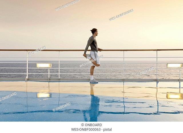 Young man doing exercises on a shipdeck, cruise ship, Mediteranean Sea