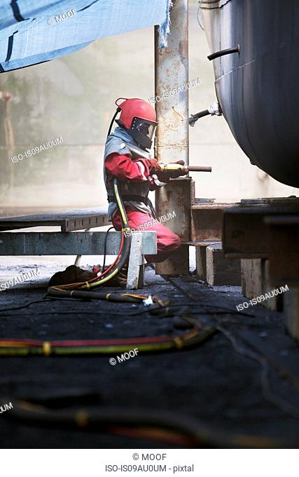 Worker sandblasting boat hull in shipyard