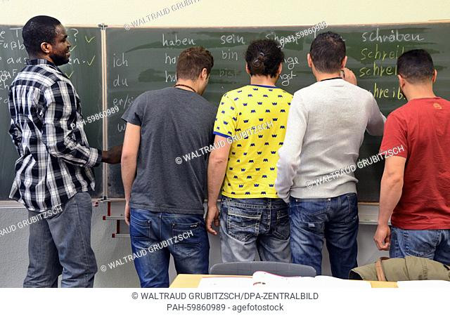 Students from Tunesia, Tanzania, Eritrea and Marocco revise texts on a blackboard in a German-language class at the community college in Leipzig, Germany