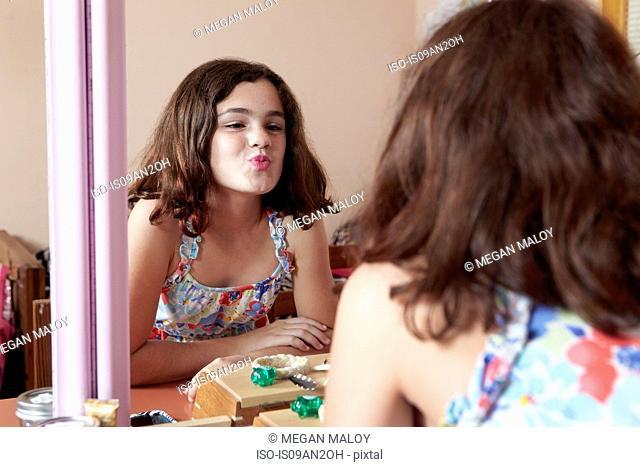 Girl puckering lips in bedroom mirror