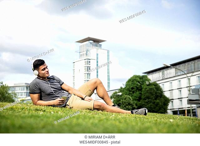 Young lying on meadow in urban park listening to music