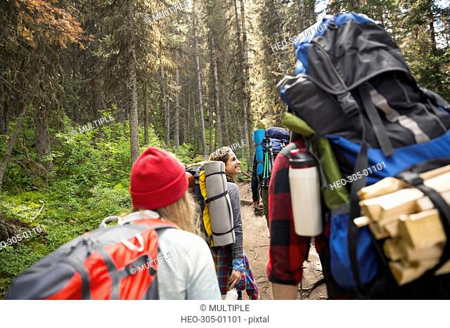 Friends with backpacks and camping equipment hiking on trail in woods