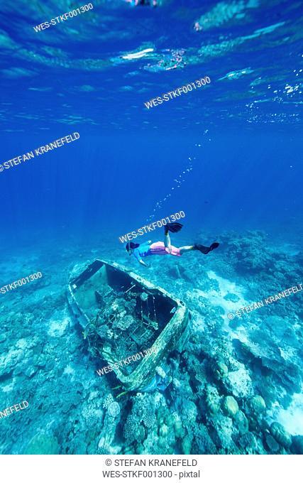 Maldives, woman snorkeling in the Indian Ocean at sunken boat