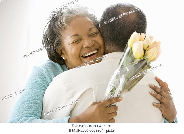 Senior African couple hugging with flowers