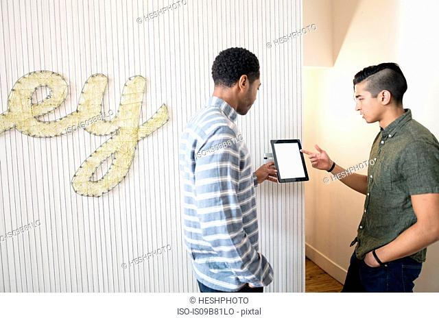 Cool young businessmen in creative office looking at digital tablet