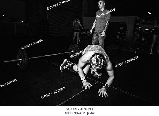 Cross training athlete kneeling in front of barbell in gym