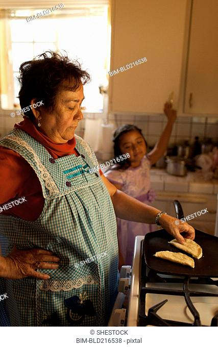 Hispanic woman cooking for granddaughter in kitchen