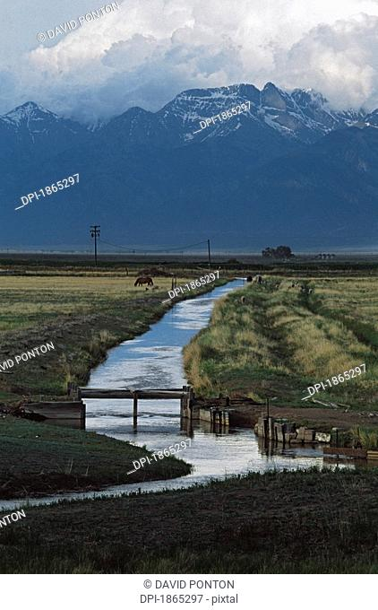 Irrigation canal with mountains and storm clouds in the background
