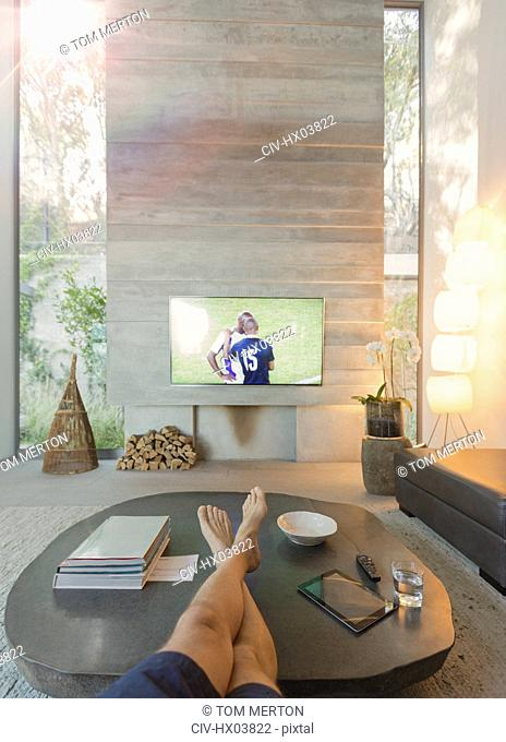 Personal perspective man watching soccer on TV in living room