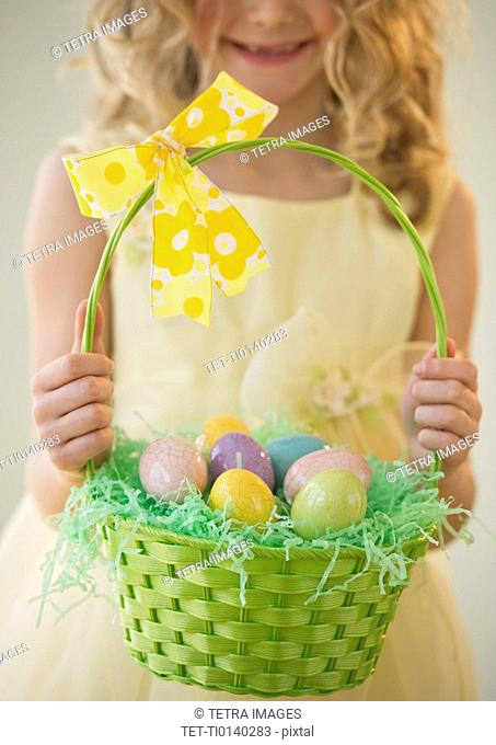 Young girl holding a basket of Easter eggs