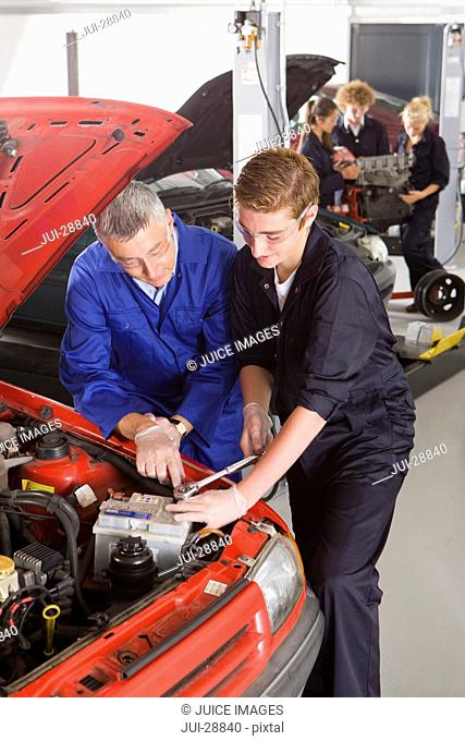 Teacher helping student repair car in automotive vocational school