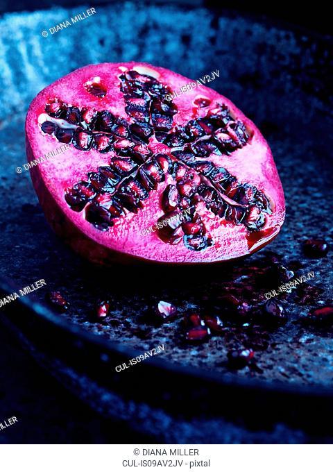 Half a pomegranate on blue plate