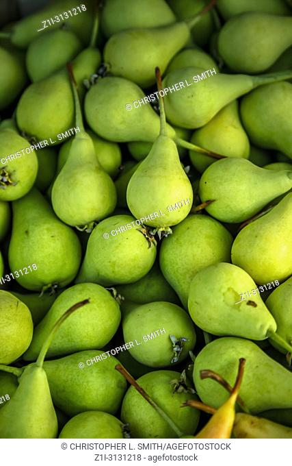 Fresh green pears for sale on a market stall