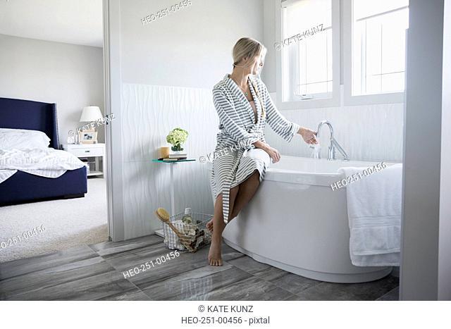 Woman in bathrobe preparing a bath in bathroom