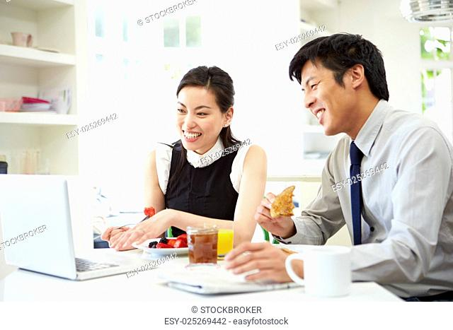Asian Couple Looking at Laptop Over Breakfast