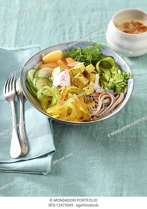 A Buddha bowl with soba noodles, turmeric tofu, vegetables and sesame seed sauce