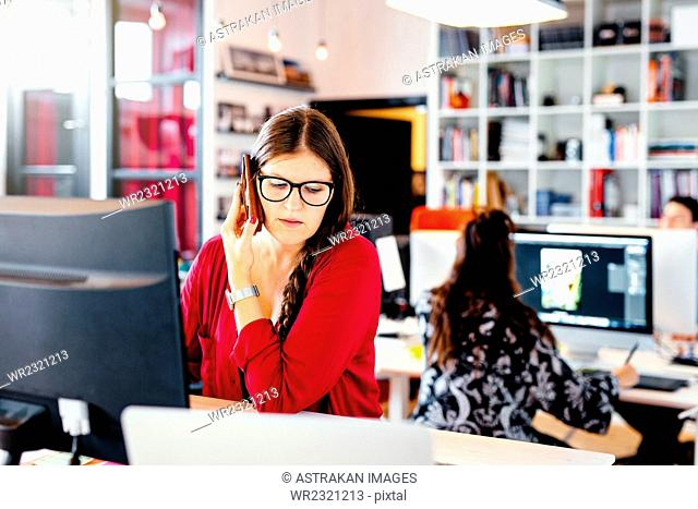 Businesswoman using smart phone at computer desk in office