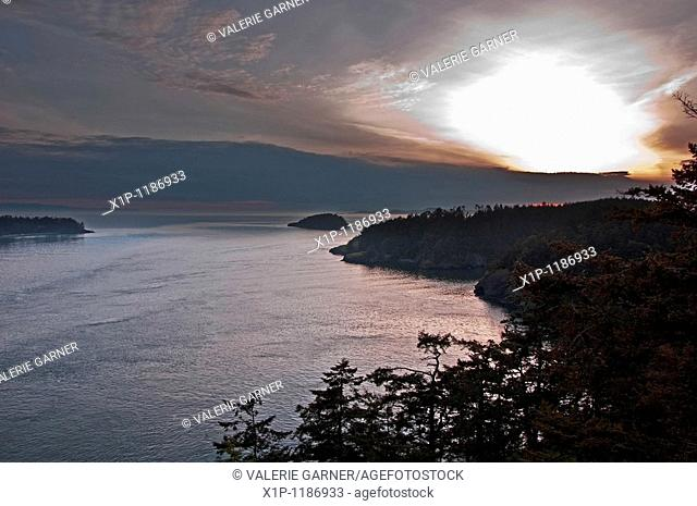 his stock image is a sunset off the San Juan Islands in Washington state Rich pink hues in the sky are reflected off the ocean water in this seascape image with...