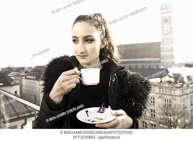 woman holding warm coffee cup outdoors in city next to touristic attraction Frauenkirche, Marienkirche, in Munich, Germany