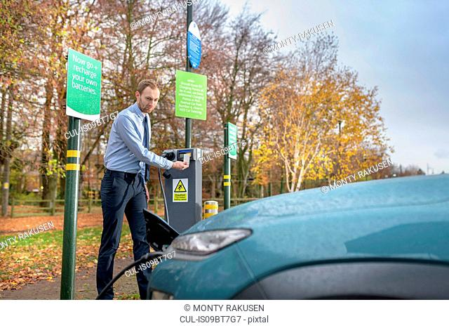 Man charging electric car at charge point, Manchester, UK