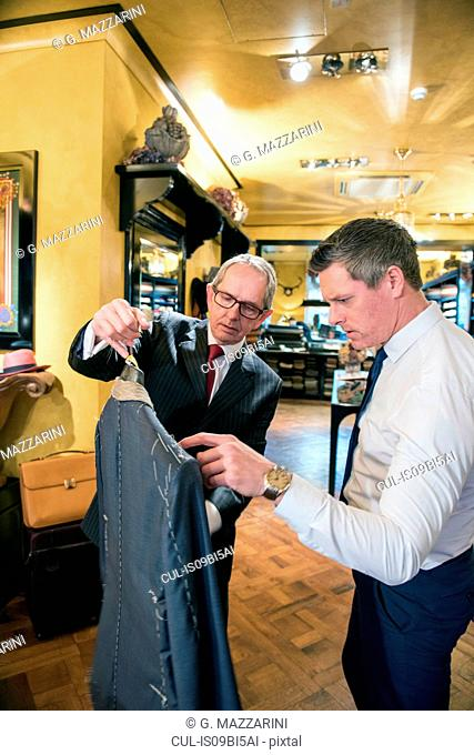 Tailor showing customer bespoke jacket in tailors shop