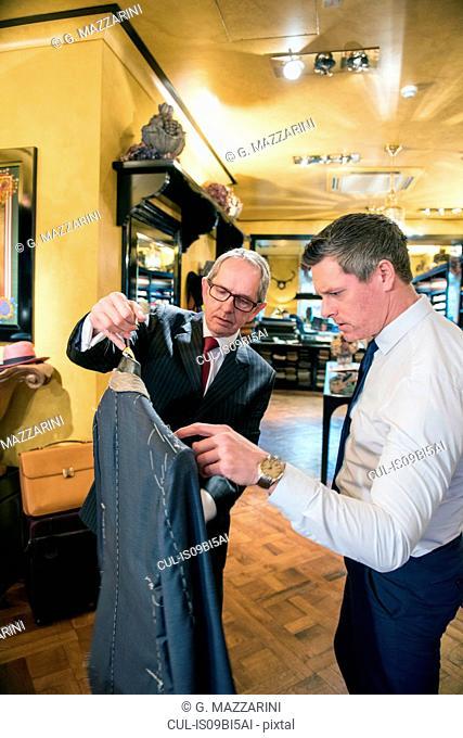 Tailor showing customer bespoke jacket in tailors shop