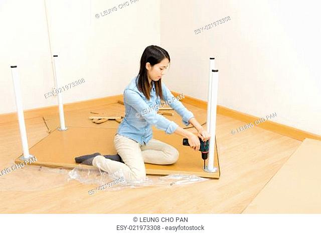 Asian woman using screwdriver for assembling furniture