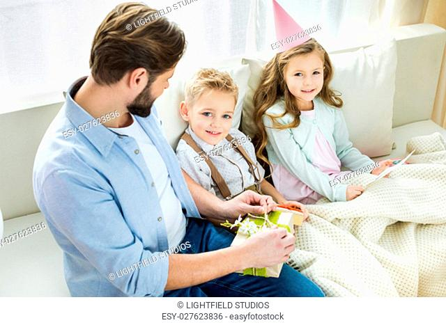 Father with two smiling children sitting on sofa with presents for Mothers day