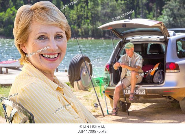 Senior Couple Enjoying Fishing Trip By Lake Together