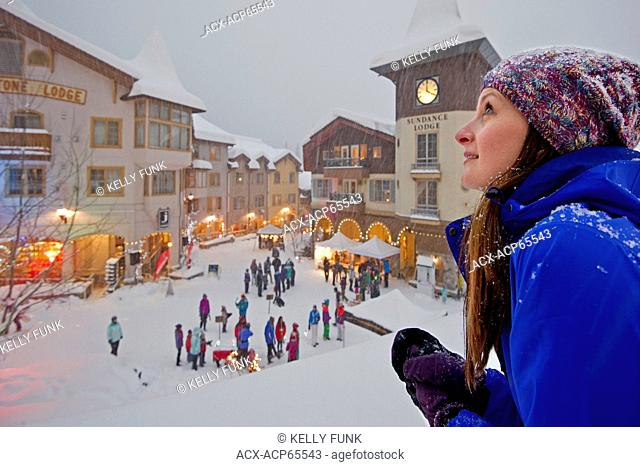 A young woman checks out the snow and festivities at Sun Peaks Resort, Sun Peaks, British Columbia, Thompson Okanagan region, Canada