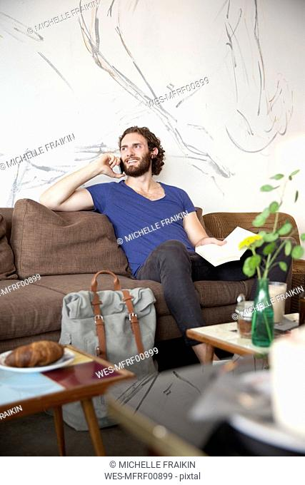 Portrait of young man on the phone sitting on couch in a coffee shop with book