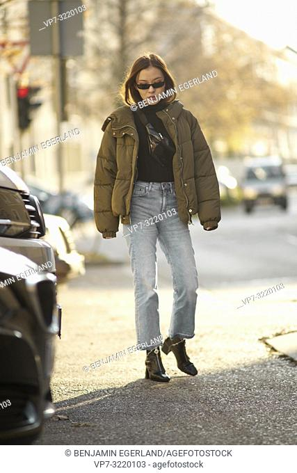 fashionable blogger woman walking in city streets with cool individual style, in Munich, Germany