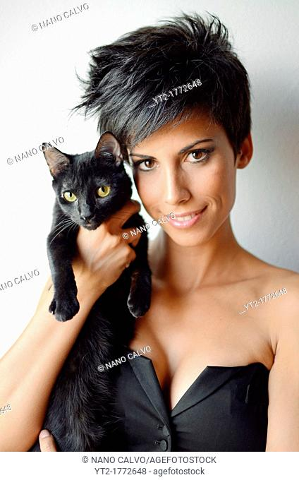 Attractive short haired woman holding a black cat