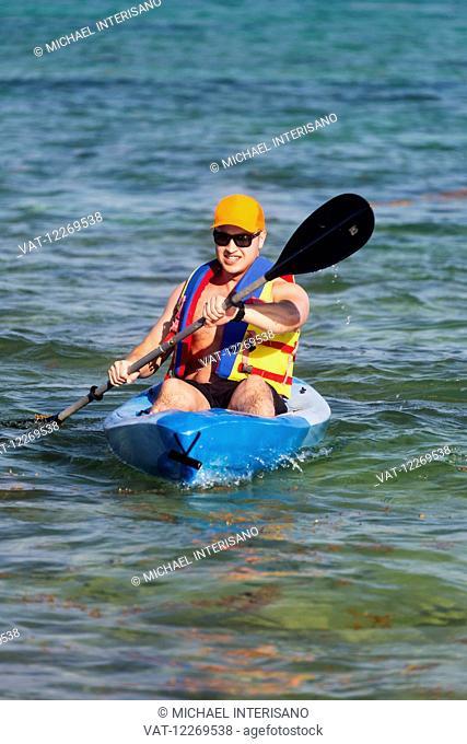 Man in kayak paddling in water; Akumal, Quintana Roo, Mexico