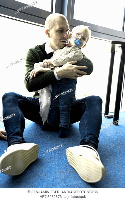father with baby toddler child sitting on blue floor at home, in Cottbus, Brandenburg, Germany