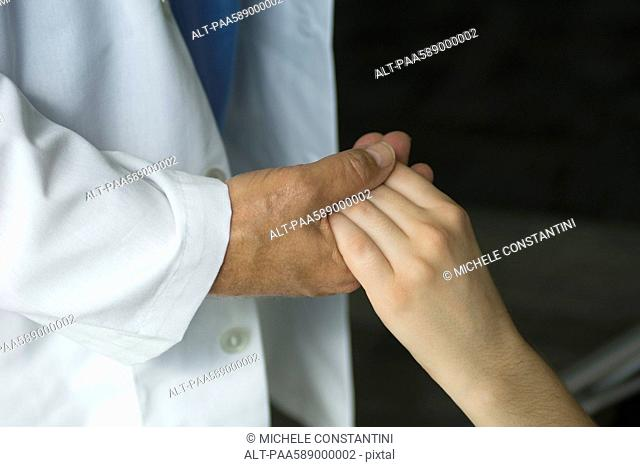 Doctor holding patient's hand, cropped