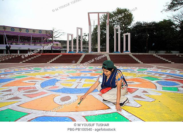 A student of the Institute of Fine Arts painting alpona color designs on the platform of Shahid Minar Martry's Monument 8 hours before the celebration of...