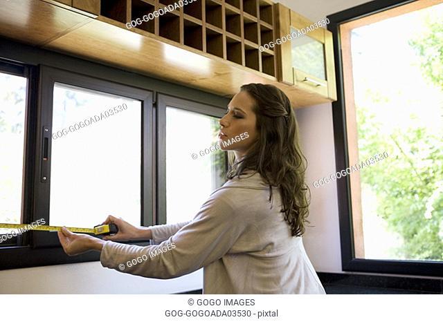 Woman measuring windows