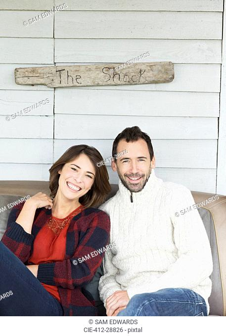 "Portrait smiling couple on porch below ""The Shack"" sign"