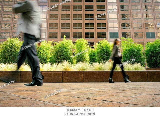 Businessman and woman walking in opposite directions