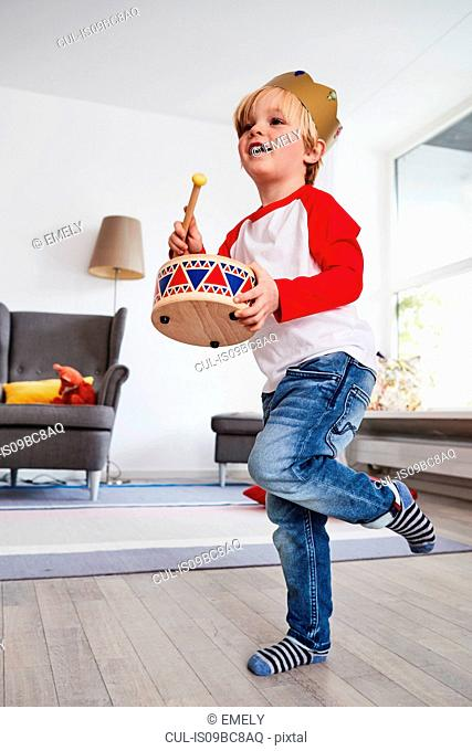 Young boy wearing cardboard crown, beating toy drum, low angle view