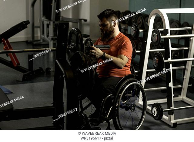 Handicapped man adjusting barbell