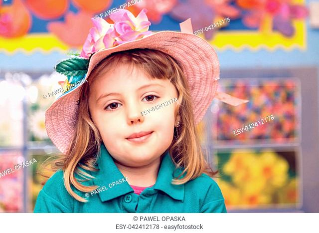 Cute little Caucasian girl wearing pink wicker hat decorated with artificial flowers