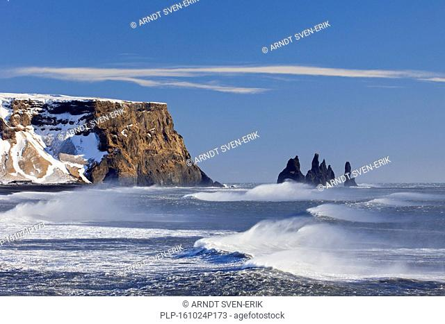 Reynisdrangar, basalt sea stacks in the snow in winter near the village Vík í Mýrdal, southern Iceland